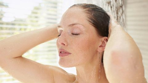 Woman washes hair under the shower - Weleda