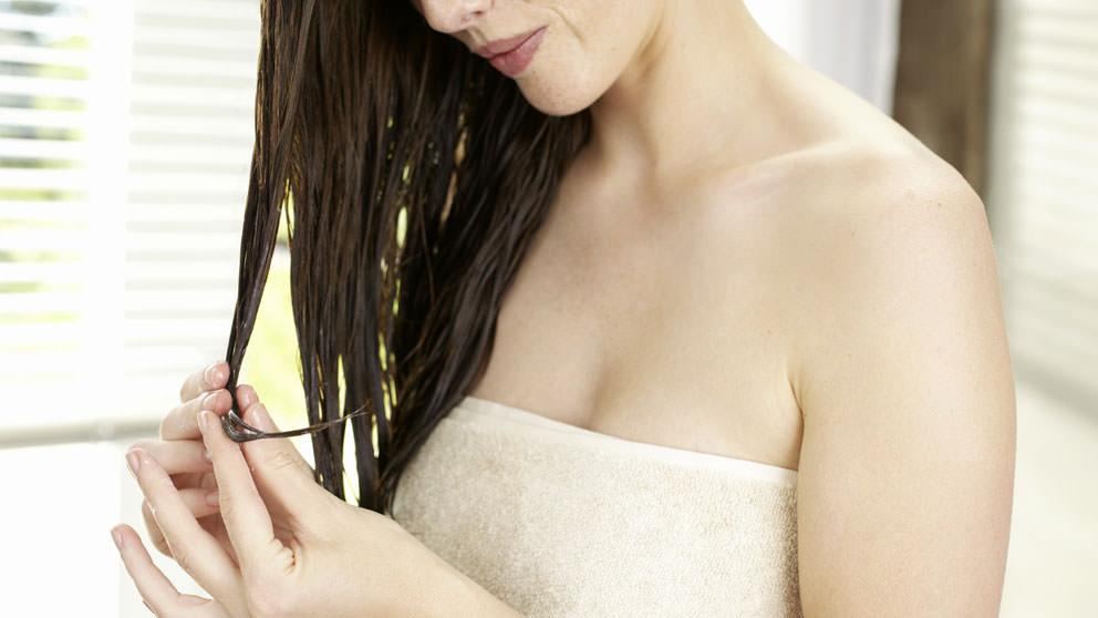 Image of Moods and Hair Care Application - Woman takes care of hair ends - Weleda