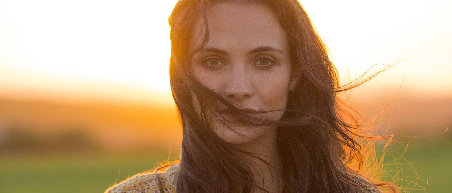 Beautiful woman on field during sunset