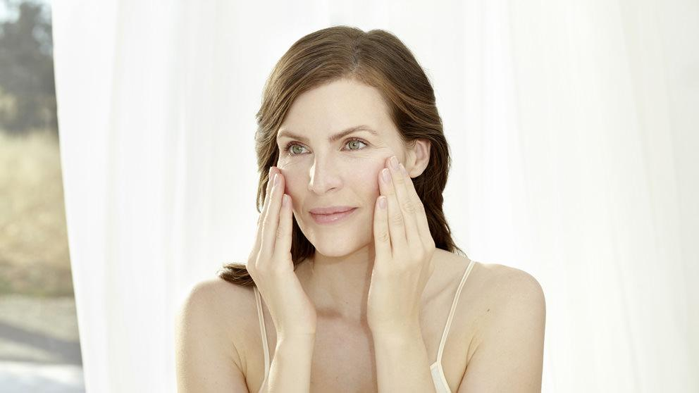 Woman gently applies Pomegranate Face Cream - Weleda