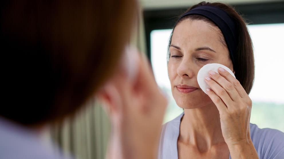 Woman cleanses face with pad